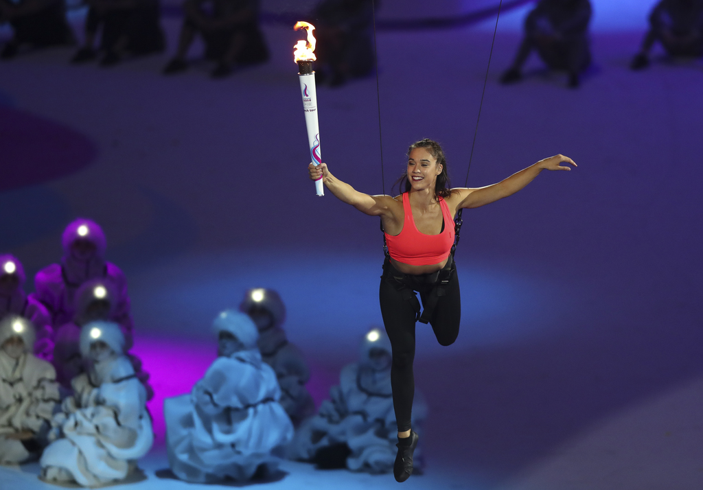 An aerialist athlete lands next to the Youth Olympic Cauldron and hands over the flame to the youngest representative of the Swiss Team present in Lausanne standing by the cauldron. The athlete can now ignite the cauldron in the stadiumin the Lausanne Vaudoise Arena at the Opening Ceremony for the Winter Youth Olympic Games, Lausanne, Switzerland, Thursday 09 January 2020. Photo: OIS/Chloe Knott. Handout image supplied by OIS/IOC.