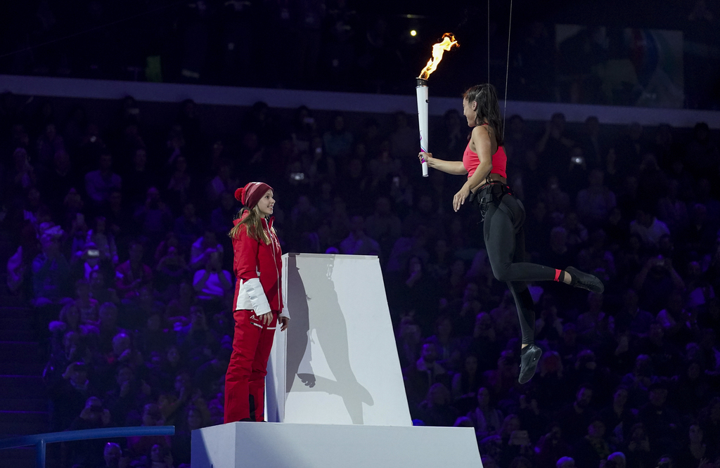 An aerialist athlete lands next to the Youth Olympic Cauldron and hands over the flame to the youngest representative of the Swiss Team present in Lausanne standing by the cauldron. The athlete can now ignite the cauldron in the stadium in the Lausanne Vaudoise Arena at the Opening Ceremony for the Winter Youth Olympic Games, Lausanne, Switzerland, Thursday 09 January 2020. Photo: OIS/Bob Martin. Handout image supplied by OIS/IOC.